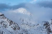 Stornappstind mountain peak emerges from clouds in winter, Flakstadøy, Lofoten Islands, Norway