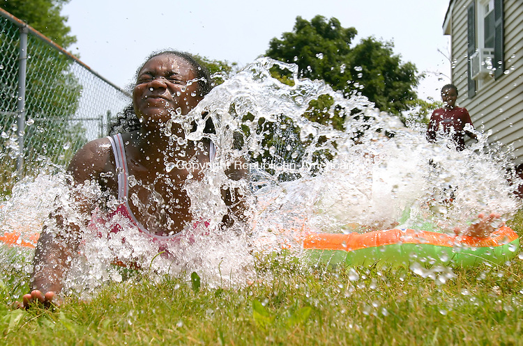 WATERBURY, CT--10 JUNE 2007--071007JS04-Brianna Jones, 10, of Waterbury, left, along with friends, Angelica Mercado, obscured by the wave of water, right, and Zahria Sanders, right in background, keep cool during Tuesday's hot weather by sliding on a water slide at Jones' house on Lincolndale Drive in Waterbury. <br /> Jim Shannon/Republican-American
