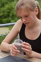 Mädchen, Kind bastelt eine Becherlupe, Beobachtungsgefäß aus 2 durchsichtigen Plastikbecher, einem Stück Styropor und Frischhaltefolie. 7. Schritt: Frischhaltefolie  wird auf den Boden eines der Plastikbecher aufgeklebt
