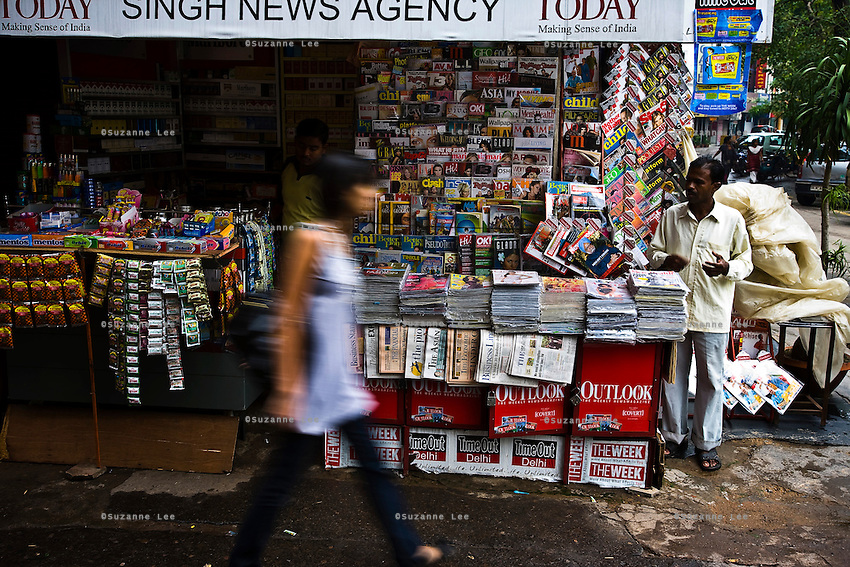 A woman walks past a newsstand in Defence Colony market, New Delhi, where Indian and Indian versions of international magazines are displayed for sale on 18 September 2008. Photo : Suzanne Lee for The National.