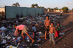 KHUTSONG, SOUTH AFRICA - OCTOBER 16: Children drop garbage on October 16, 2012, in Khutsong, South Africa. Khutsong, a black township. is located about 56 miles west of Johannesburg, and surrounded by gold mines. Because of recent strikes many mineworkers has been fired which is making the poverty worse here. The communal toilets are dirty and often broken. (Photo by Per-Anders Pettersson)