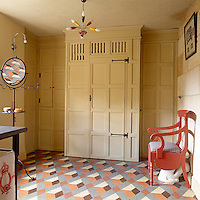 A blend of contrasting styles in the bathroom with a 1950s light fitting, hand-painted geometric floor and the toilet cunningly disguised as an antique commode