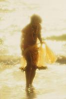 Hawaiian man with his throw net on the ocean's edge at sunset.