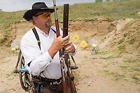 Competitor takes his weapon for inspection during the Cowboy Action Shooting European Championship in Dabas, Hungary on August 11, 2012. ATTILA VOLGYI