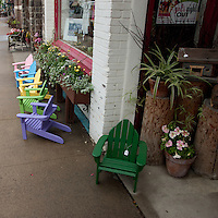 Children's colorful outdoor seating line the sidewalk in front of the establishment selling them.