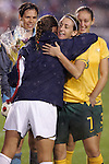 27 April 2008: Heather Garriock (AUS) (7) receives a bouquet of flowers and a hug from U.S. captain Christie Rampone (in blue) in honor of reaching her 100th cap, or international appearance. The United States Women's National Team defeated the Australia Women's National Team 3-2 at WakeMed Stadium in Cary, NC in a rain delayed women's international friendly soccer match.