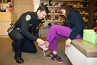 Santa Monica Police Captain Daniel Salerno helps Magali Rivera, 11, try on a pair of Shoes during the Salvation Army Santa Monica Corps 28th Annual Sears Holiday Shopping Spree on Tuesday, November 13, 2012.