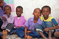 Jambiani, Zanzibar, Tanzania.  Schoolboys in Class.  The alphabetic letters on the wall show that they are learning to read Arabic, so they can read the Koran.