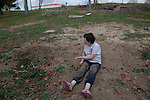Marylynne Hall, 13, plays in the dirt outside her family's new home. After being homeless for two and a half months, the Hall family is about to move into a trailer.