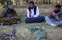 Foot soldiers from the Wardak Mobile Patrol Unit use mobile phones with un-registered sim cards to communicate with other Taliban under the shade of a garden in a safe haven property