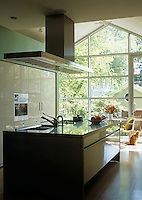 A small eating area in a contemporary kitchen is located beside a dramatic floor-to-ceiling wall of windows opening onto the garden