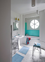In this bathroom a contemporary bath is enclosed in an alcove lined with turquoise mosaic tiles beneath a circular window