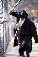 Man in suit swinging nightstick