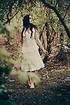 Young lady with long black curly hair in a white dress walking among the trees