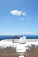 A pair of chairs draped in a white sheet on the roof terrace forms a sculptural shape against the blue horizon