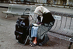 00779_06, Lourdes, France, 10/1989, FRANCE-10068. A woman reads with her belongings beside her.<br />
