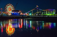 The Pacific Park ferris wheel reflects along the shoreline during low tide on Wednesday, Dec 4, 2013.
