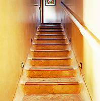 This staircase features polished tadelakt walls terracotta tiled steps and is illuminated with brass down lighters