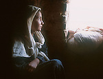 An ethnic Uzbek girl looks out the window of her family's home in the Shamshatoo refugee camp..