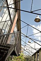 Steel buttresses between the buildings create pleasing geometric shapes above the communal walkway below