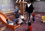 Berkeley, CA Caregivers playing with multiethnic children on playground at day care center