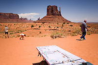 Tourists pass tables of Navajo crafts at Monument Valley Navajo Tribal Park in southern Utah. The park, operated by teh tribe, was once a popular set for western films of the 1930s through 60s. It is immensely popular among European tourists. (Kevin Moloney for the New York Times)