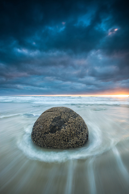 A dramatic morning sky and receeding waves around a Moeraki Boulder, Coastal Otago, South Island, New Zealand - stock photo, canvas, fine art print