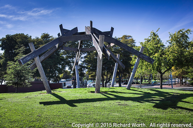 A creation from wood at an urban park.  Six massive wooden poles rise from the ground and support a wooden web, a geometric hodgepodge in pine, perhaps.