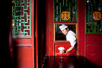 A member of the kitchen staff places a cold desert through a serving hatch at The West Lake Restaurant. Able to seat up to 5,000 people at one sitting, The West Lake Restaurant is the biggest Chinese restaurant in the world. Each week its diners, who staff are taught are 'the bringers of good fortune', devour 700 chickens, 200 snakes, 1,200 kgs of pork and 1,000 kgs of chillis. Its 300 chefs cook in five kitchens and its staff total more than 1,000.It is fully booked most nights.