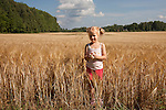 Young Girl Standing by Cornfield, Estonia, Europe