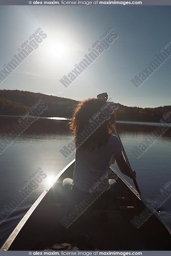 Young woman canoeing on a lake in fall. Arrowhead Provincial Park, Muskoka, Ontario, Canada.