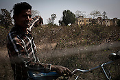 A cyclist points to the newly constructed rehabilitation colony in Belgharia, outskirts of Dhanbad, Jharkhand, India. Residents living in Bokapahari will be relocated to these small apartments. Photo: Sanjit Das