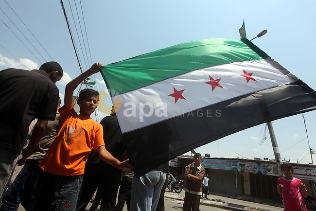 Palestinian children hold a Syrian revolution flag during a protest against Syria's President Bashar al-Assad and in support of Syrian civilians at Nusseirat refugee camp in the central Gaza Strip on June 22, 2012. The French foreign ministry called on June 22, for the Syrian military to desert en masse the day after a Syrian air force colonel defected after landing his MiG fighter in Jordan. Photo by Ashraf Amra