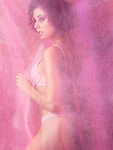 Sensual glamour photo of a young beautiful woman in lingerie standing behind flowy sheer pink curtain