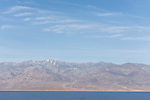 Death Valley National Park, California; a view of the Panamint mountain range and Telescope peak with snow on top in early morning sunlight, from across the Badwater Basin salt flats which are still in shadow from the Amargosa mountain range to the east