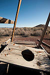 Outhouse and hole falling apart in the landscape at the Baldwin Mine, Jackson Range, Nev.