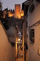 The Comares Tower, built in the 14th century under Muhammed V, Alhambra, seen from a narrow street in El Albayzin, the Moorish old town of Granada, Andalusia, Southern Spain. The Alhambra was begun in the 11th century as a castle, and in the 13th and 14th centuries served as the royal palace of the Nasrid sultans. The huge complex contains the Alcazaba, Nasrid palaces, gardens and Generalife. Granada was listed as a UNESCO World Heritage Site in 1984. Picture by Manuel Cohen