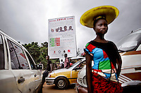 A woman walks past parked cars and a large billboard honours the local doctors, including national hero Doctor Sheik Umar Khan, who have died in the fight against ebola.