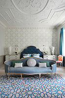 The master bedroom retains the original Georgian architectural details including the original plasterwork on the ceiling, which dates back to the 1750s.  Blocks of colour, for example on the bed, sofa and curtains, have a balancing effect on the bold pattern and the blue and cream rug is by Martin Lawrence Bullard.