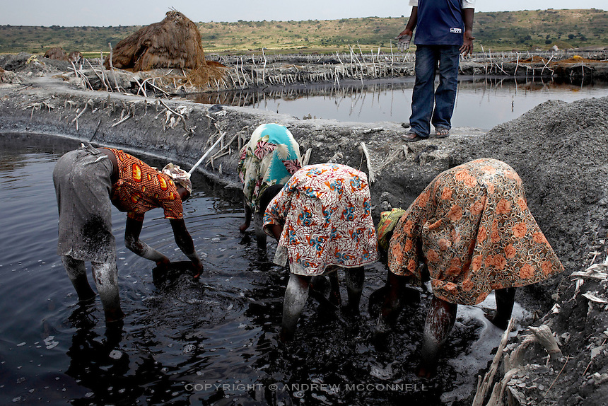 Women scrape salt from the bed of a pan at Lake Katwe.