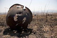 A soldier's helmet remains more than a decade after fighting stopped on this battlefield in the Martuni region of Azerbaijan.  In the background, deminers with the Halo Trust work to clear the area of anti-tank mines and unexploded ordnance.