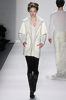 Model walks runway in an ivory wool felt mii storm coat w/curly lamb collar, ivory bamboo v-neck T's+ velvet leggings,  from the Zang Toi Fall 2012 &quot;Glamour At Gstaad&quot; collection, during Mercedes-Benz Fashion Week New York Fall 2012 at Lincoln Center.