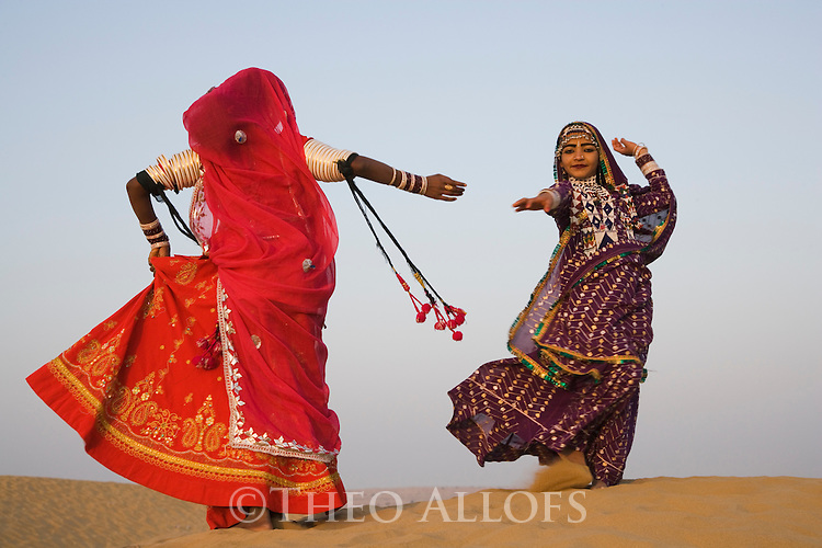 Rajasthani dancers in traditional costumes performing on sand dunes in the Thar Desert; Camel driver with camels in background; Rajasthan, India ---Model Released