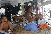 A family living next to the sea, on the South Pacific island of Kiribati. They have re-enforced their property with a sea wall made of sand bags to stop the encroaching sea from eroding their land.
