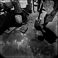 Luanda, Angola, May 20, 2006.Bairro Pescadores. taking water from one of the rare 'clean' water reservoirs.  Between February and June 2006, more than 30000 people were infected with cholera in Angola's worse outbreak ever; more than 1300 died.