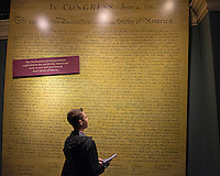 A teenage boy (model released) reviews a giant copy of the Declaration of Independence at the American History Museum in Washington DC.