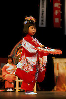 Young Japanese Girl Dancer from Ikuta Shinto Shrine in Japan wearing a Kimono and dancing Traditional Fan Dance Performance on Stage (No Model Release Available)