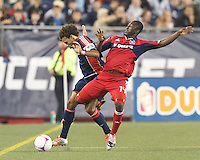Chicago Fire midfielder Patrick Nyarko (14) gets tangled in dribbling New England Revolution defender Kevin Alston (30). In a Major League Soccer (MLS) match, the New England Revolution (blue) defeated Chicago Fire (red), 1-0, at Gillette Stadium on October 20, 2012.