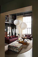 The double-height ceiling of the large living room provides ample space for a mezzanine library and dwarfs the giant vase in the corner, a design by Jean-Marie Masseau