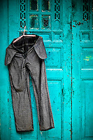 A pair of freshly washed bluejeans hangs on a blue door to dry in the midday sun.